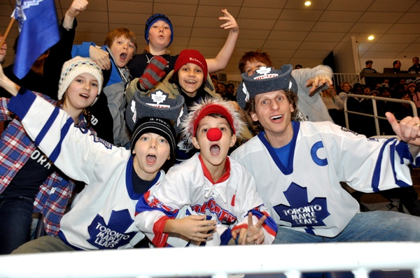 A group of young adults dressed up in hockey fan gear at a hockey game.
